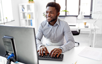smiling young man in office using the computer